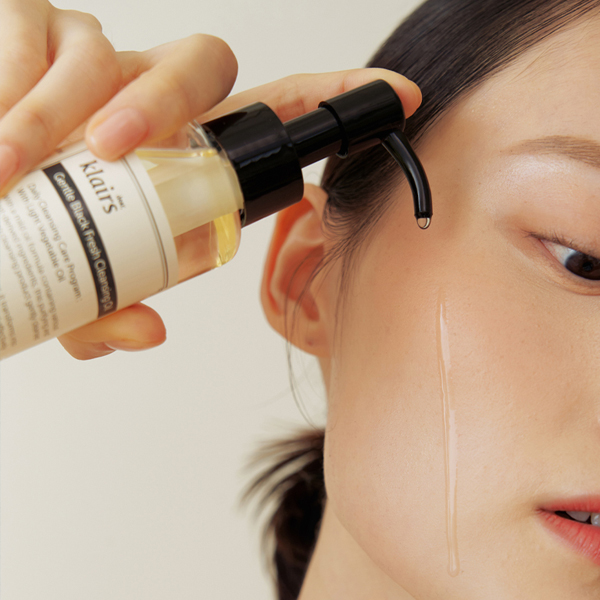 woman applying an oil cleanser (waterless skincare)